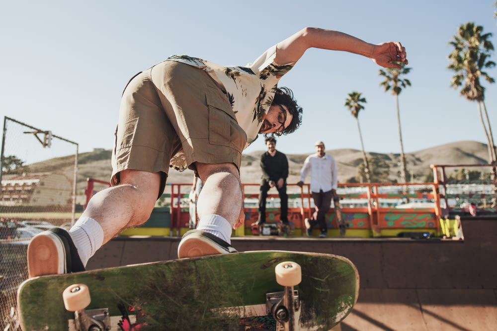 man in green camouflage shirt and brown shorts jumping on brown wooden fence during daytime