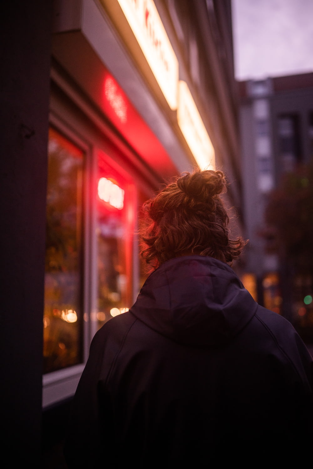 woman in black hoodie standing near glass window during night time