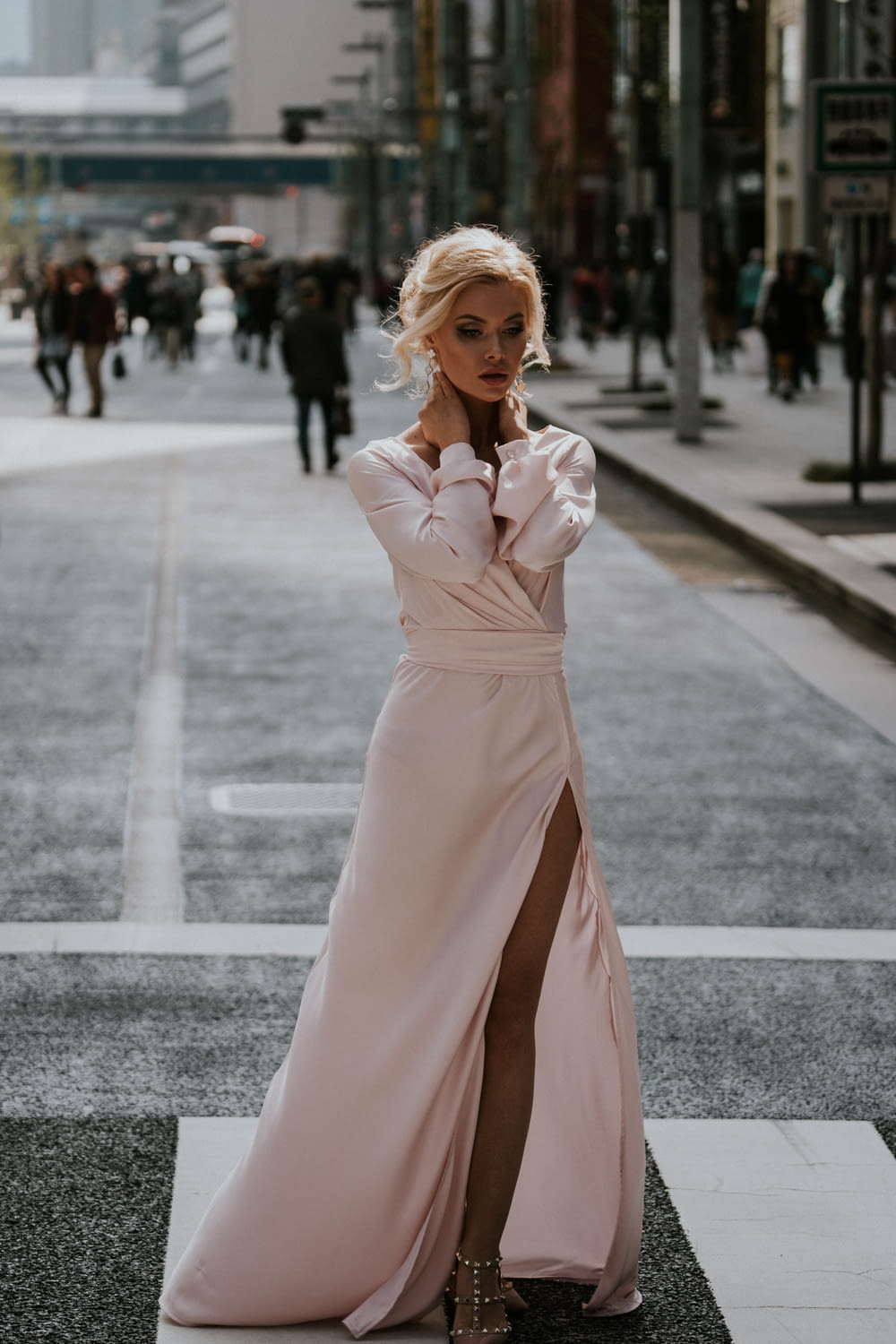 woman in pink long sleeve dress standing on road during daytime