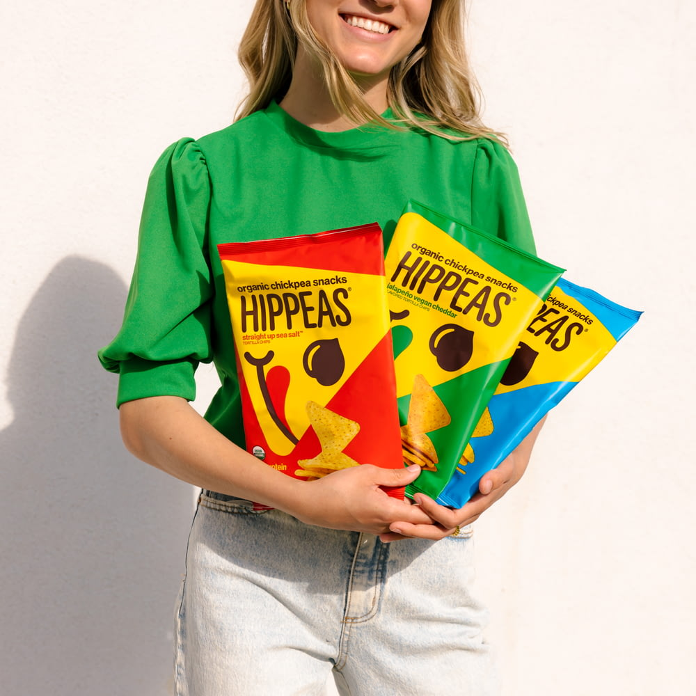 woman in green and yellow crew neck t-shirt holding yellow and red happy birthday banner