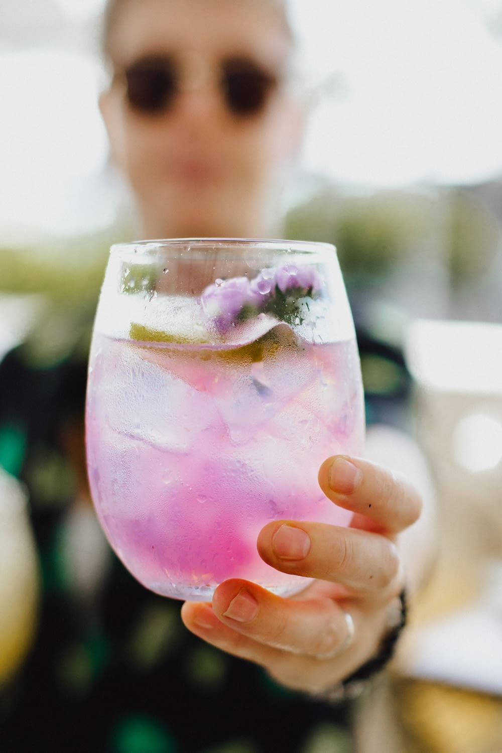 person holding clear drinking glass with pink liquid