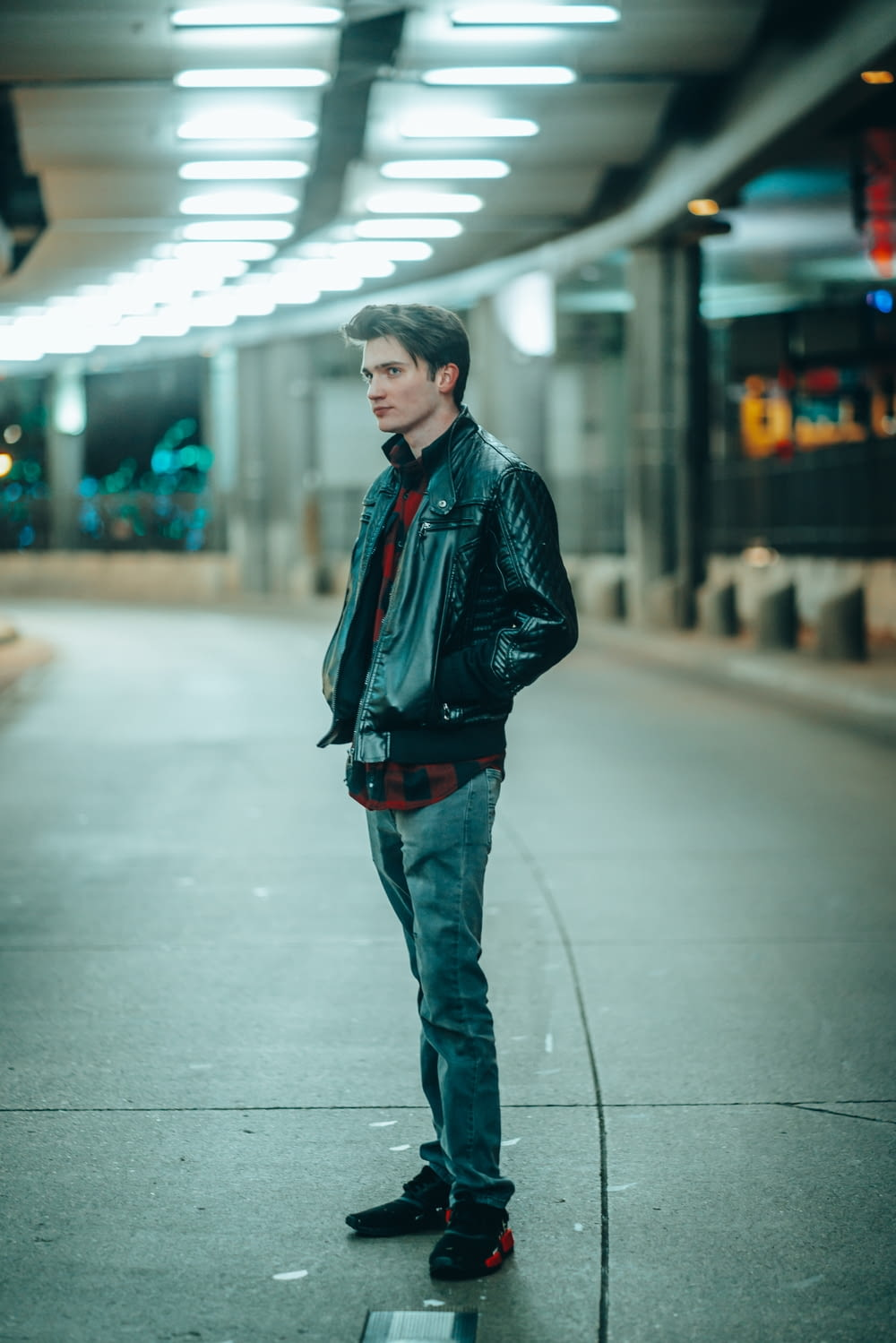 man in black leather jacket standing on sidewalk during daytime