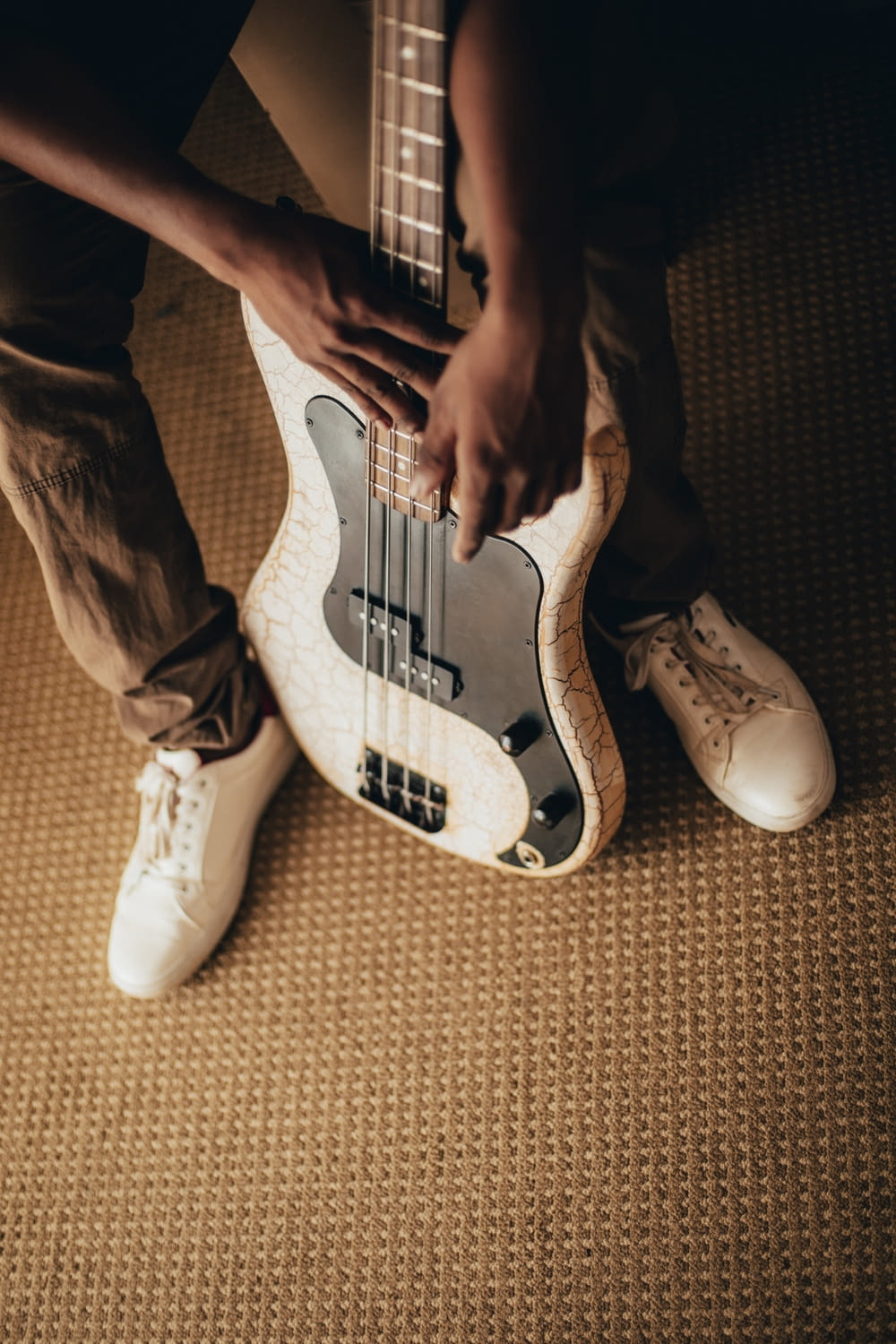 person holding white and black stratocaster electric guitar