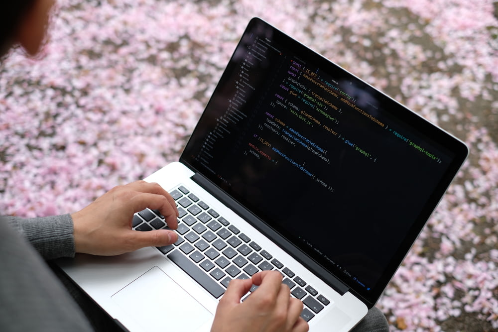 person using macbook pro on pink and white floral textile
