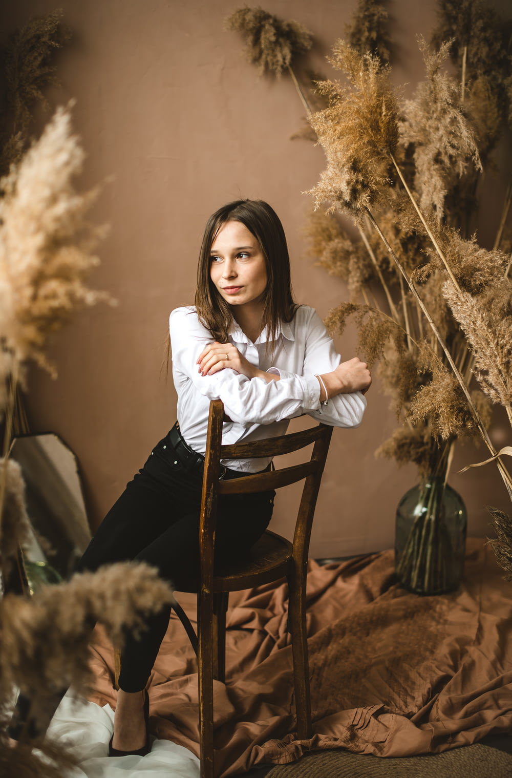 woman in white long sleeve shirt sitting on brown wooden chair
