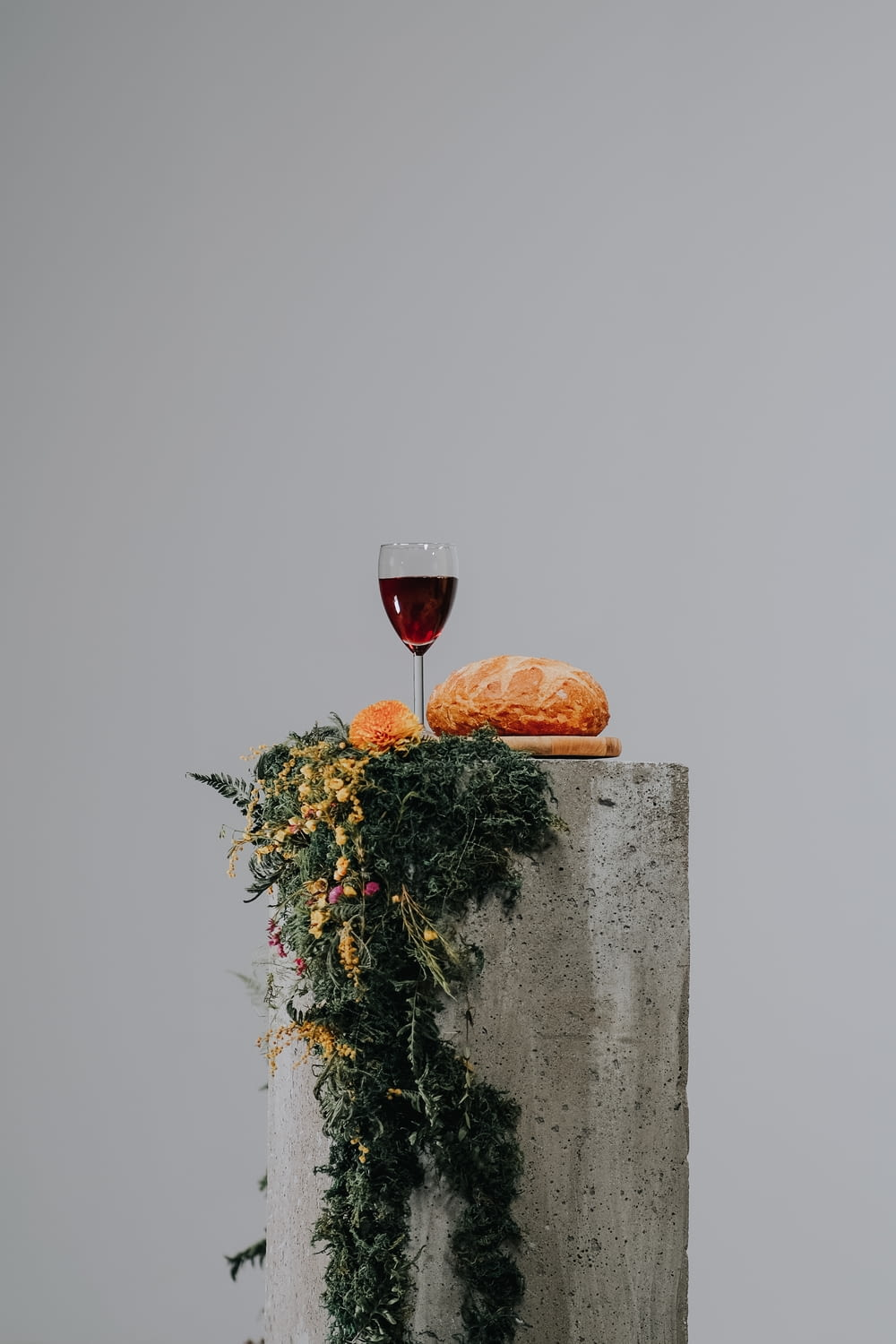 red wine in clear wine glass on gray concrete wall