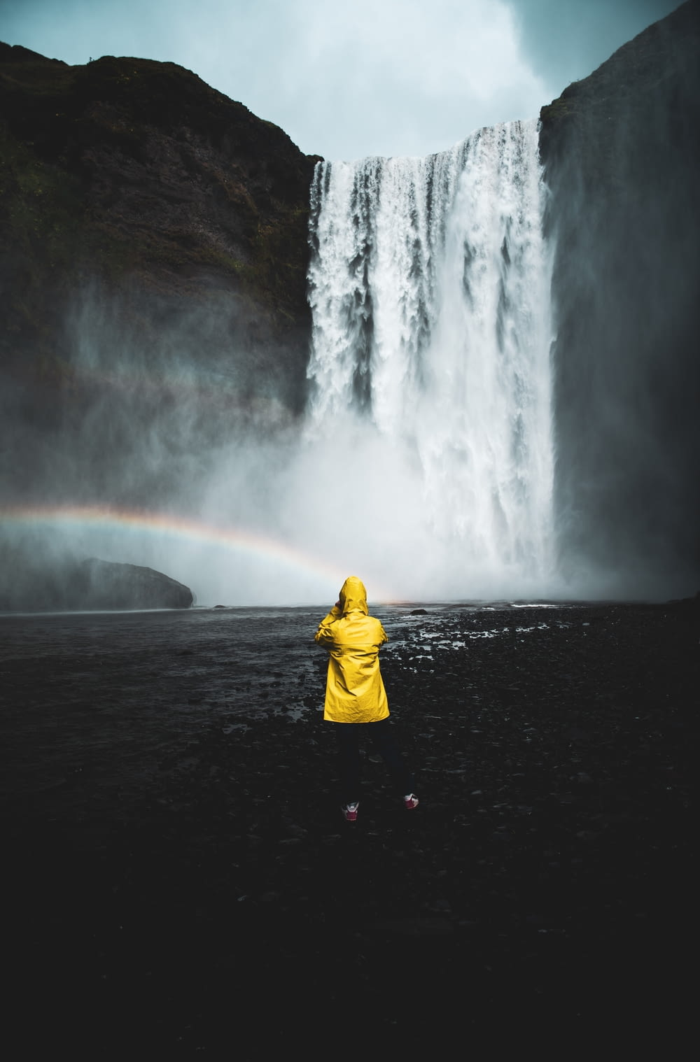 person in yellow hoodie standing in front of waterfalls