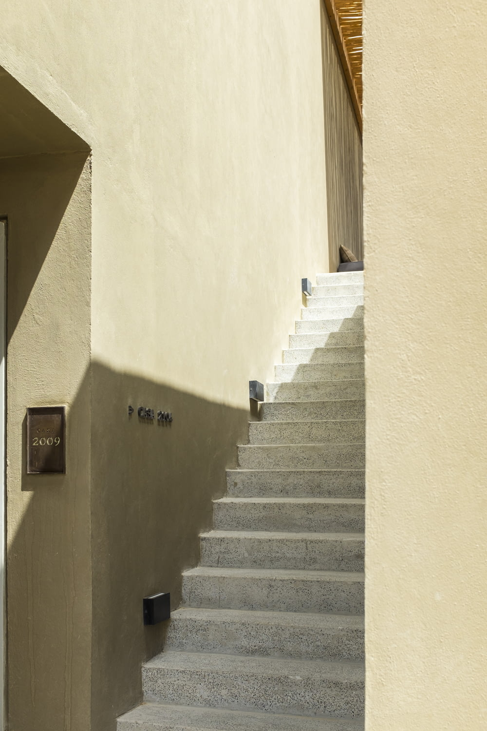 white concrete staircase with brown wooden door