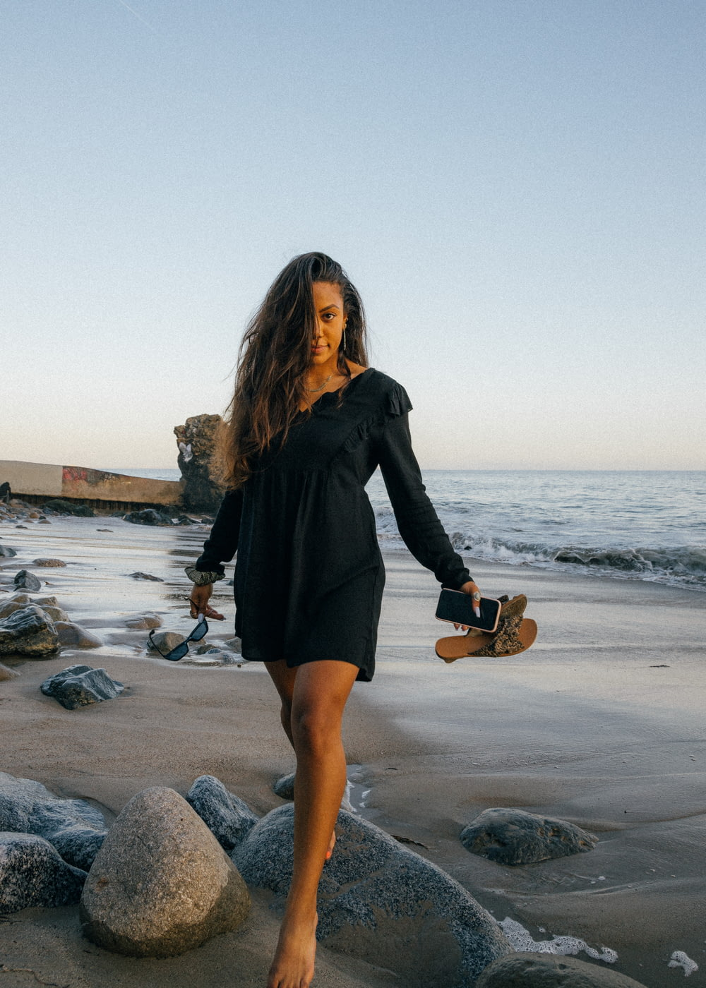 woman in black long sleeve dress holding brown acoustic guitar standing on gray rock near body