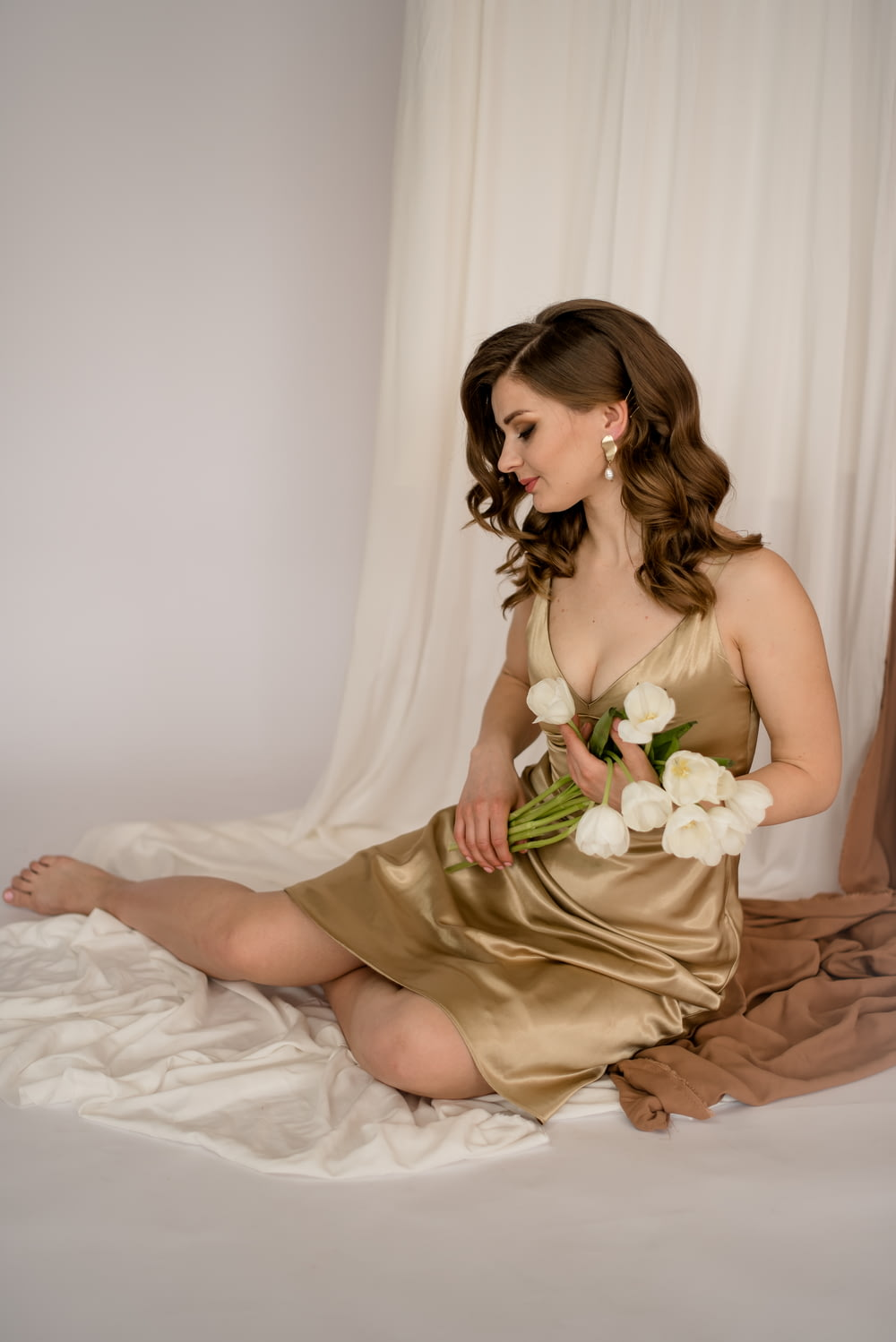 woman in brown spaghetti strap dress sitting on bed