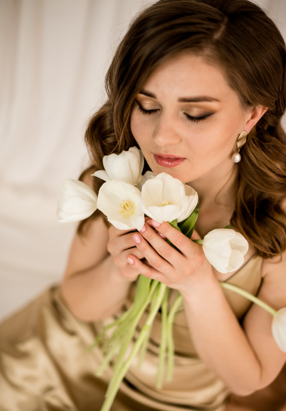 woman in white tank top holding white flowers