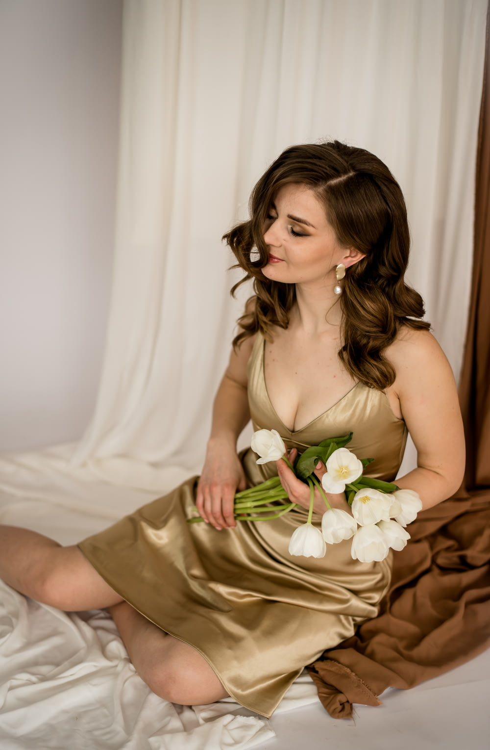 woman in beige spaghetti strap dress holding white rose bouquet