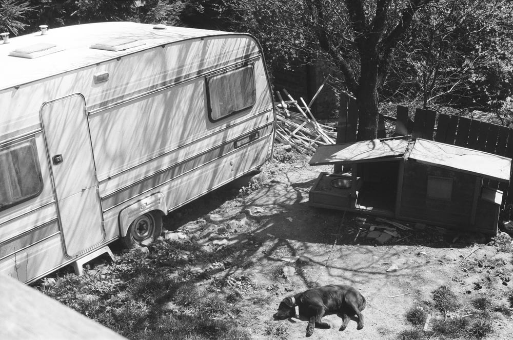 grayscale photo of white and brown camper trailer