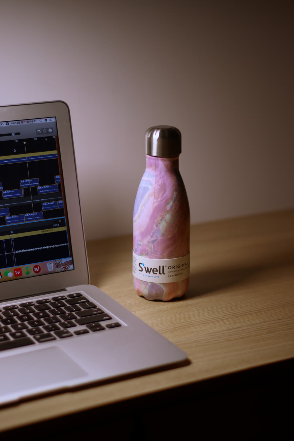 purple and white plastic bottle beside macbook pro