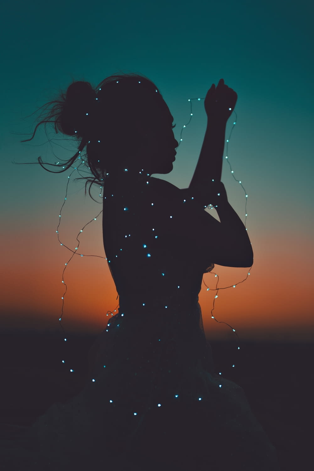 silhouette of woman holding her hair during sunset