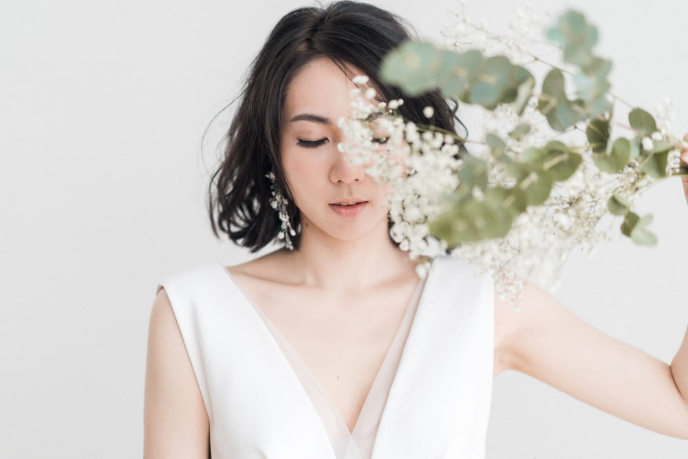 woman in white sleeveless top with white flower on ear