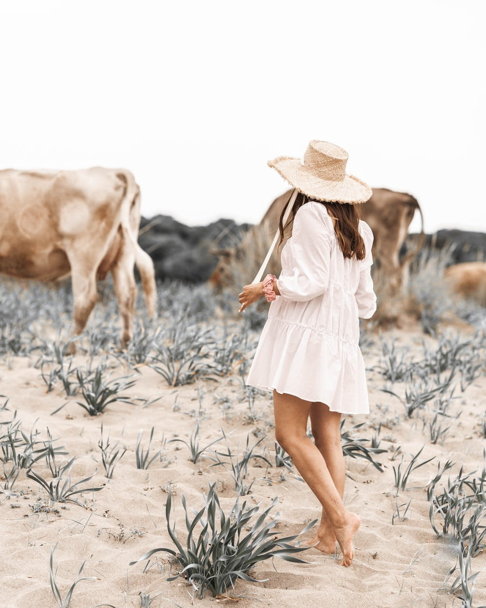 woman in white dress and brown hat walking on brown sand during daytime