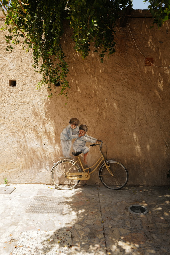 man and woman riding on bicycle beside brown concrete wall during daytime