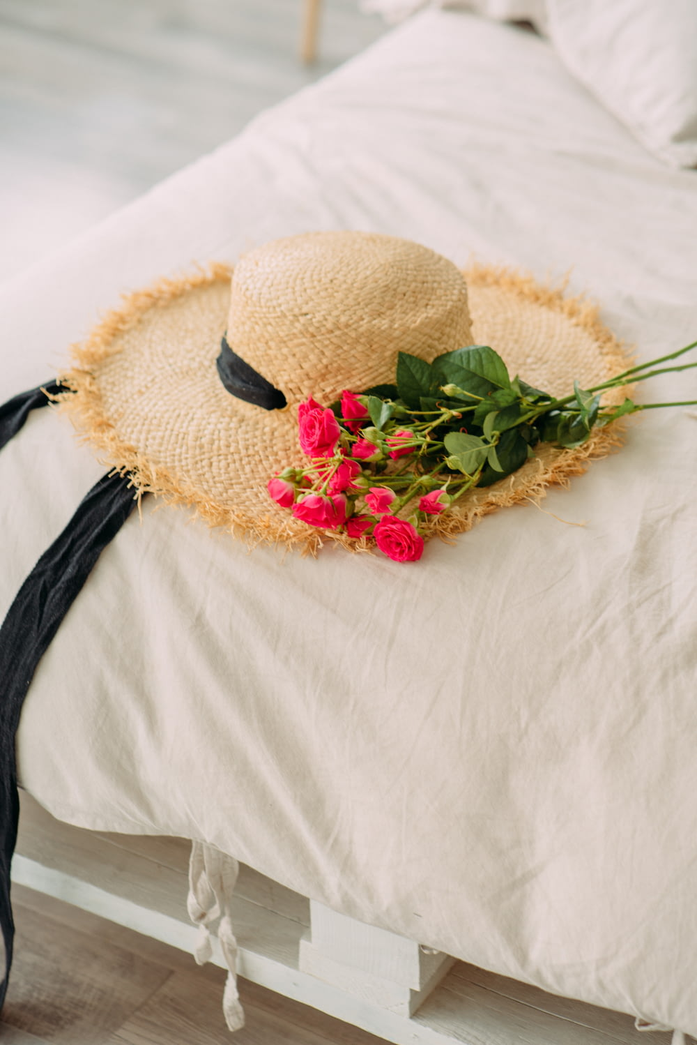 brown woven hat with red and green flower on white textile