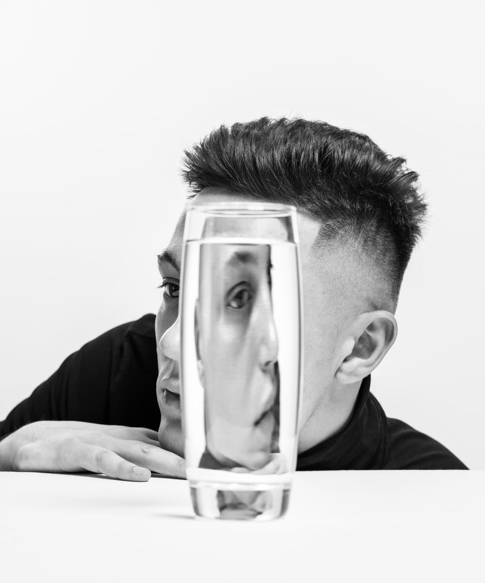 man in black shirt holding clear glass container