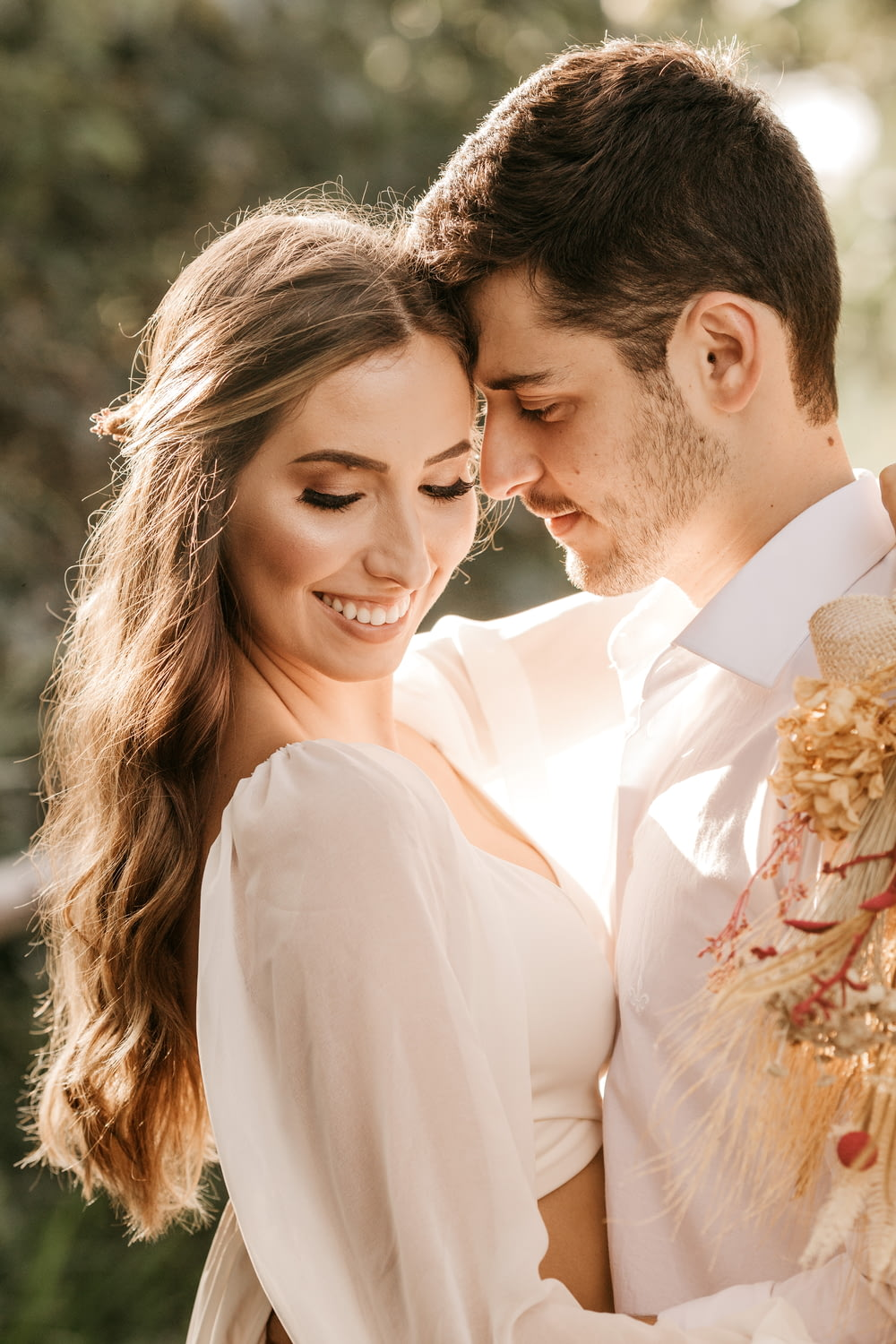 man in white suit kissing woman in white dress