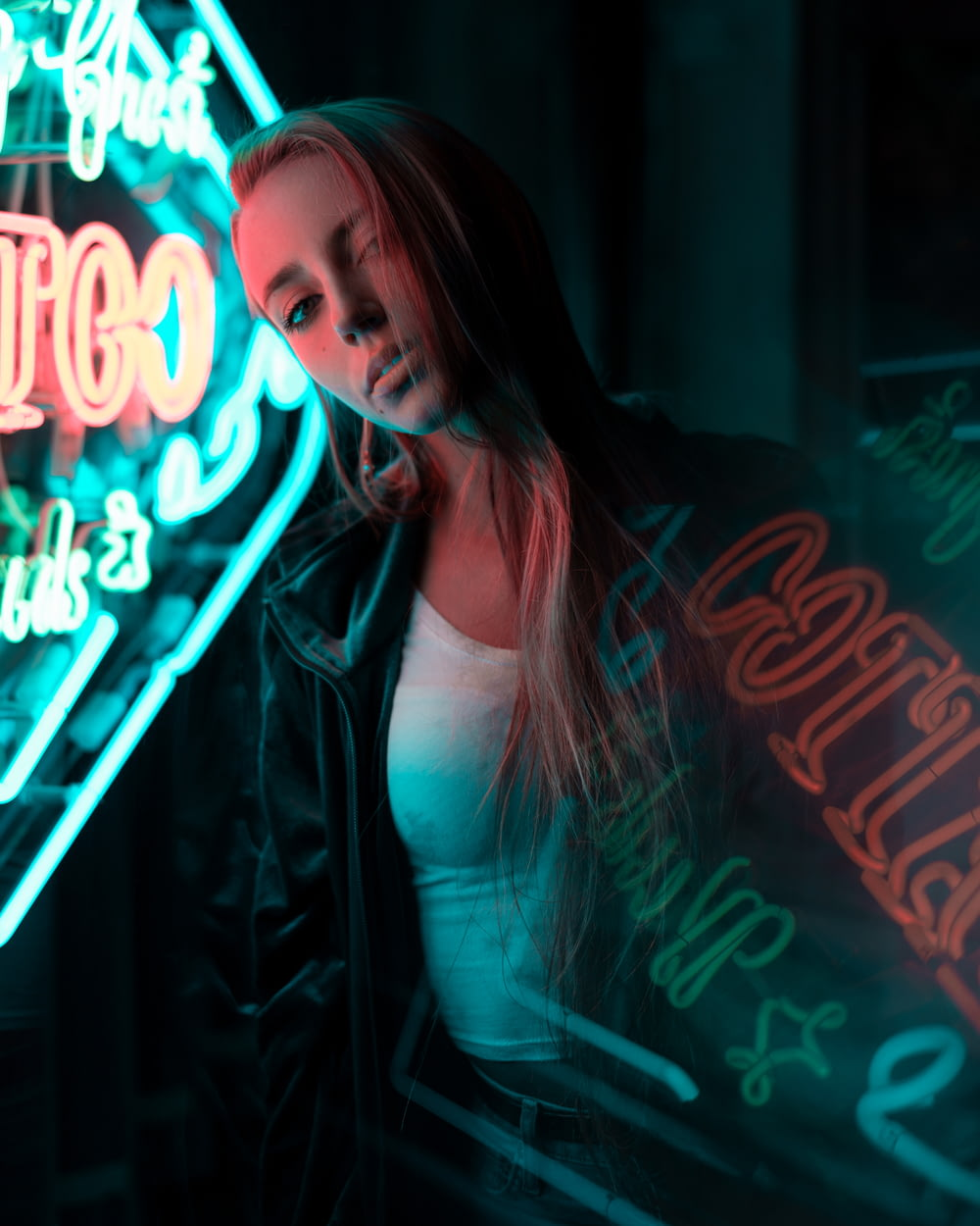 woman in white tank top standing near neon signage