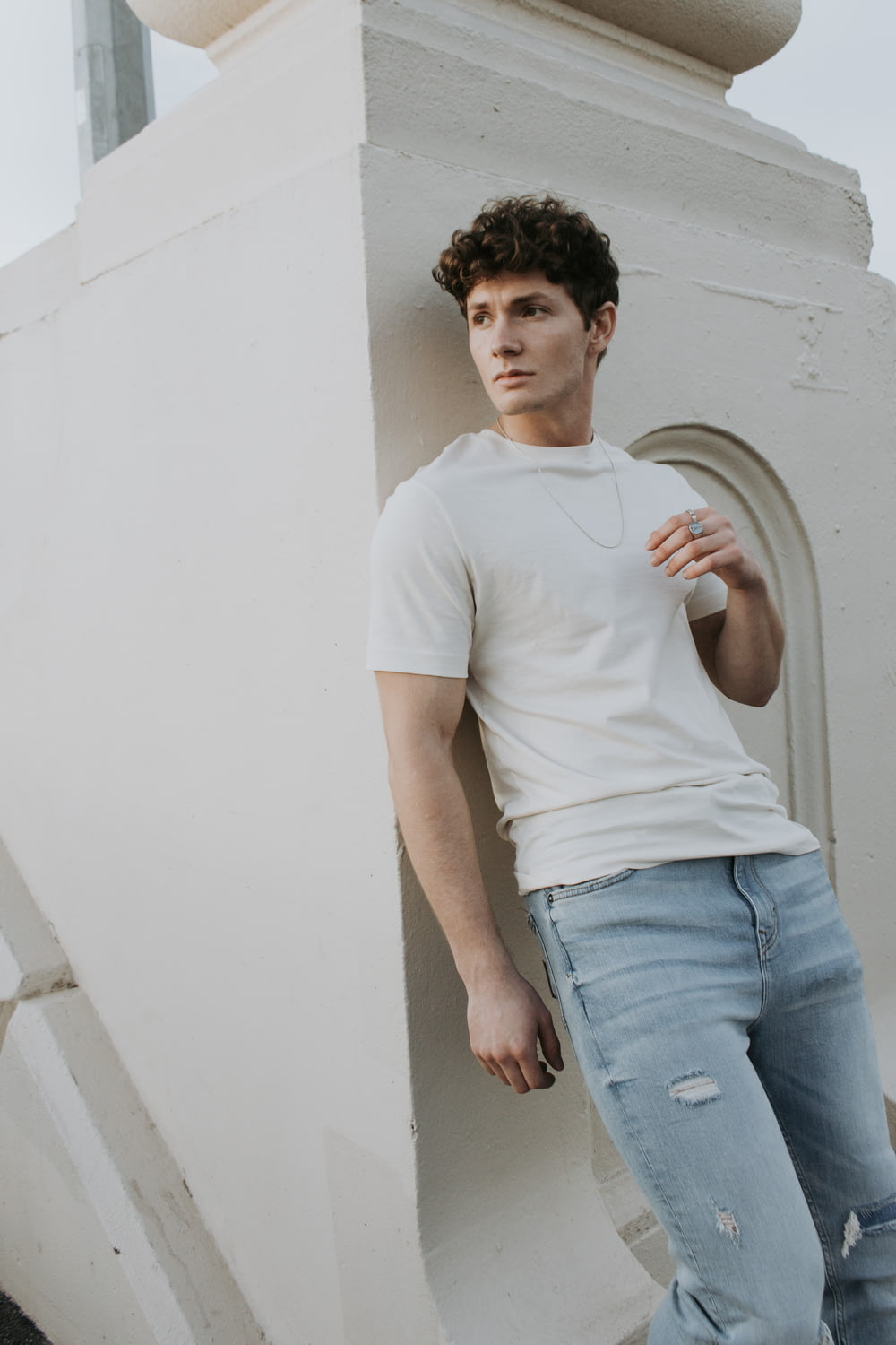 man in white crew neck t-shirt and blue denim jeans standing beside white wall