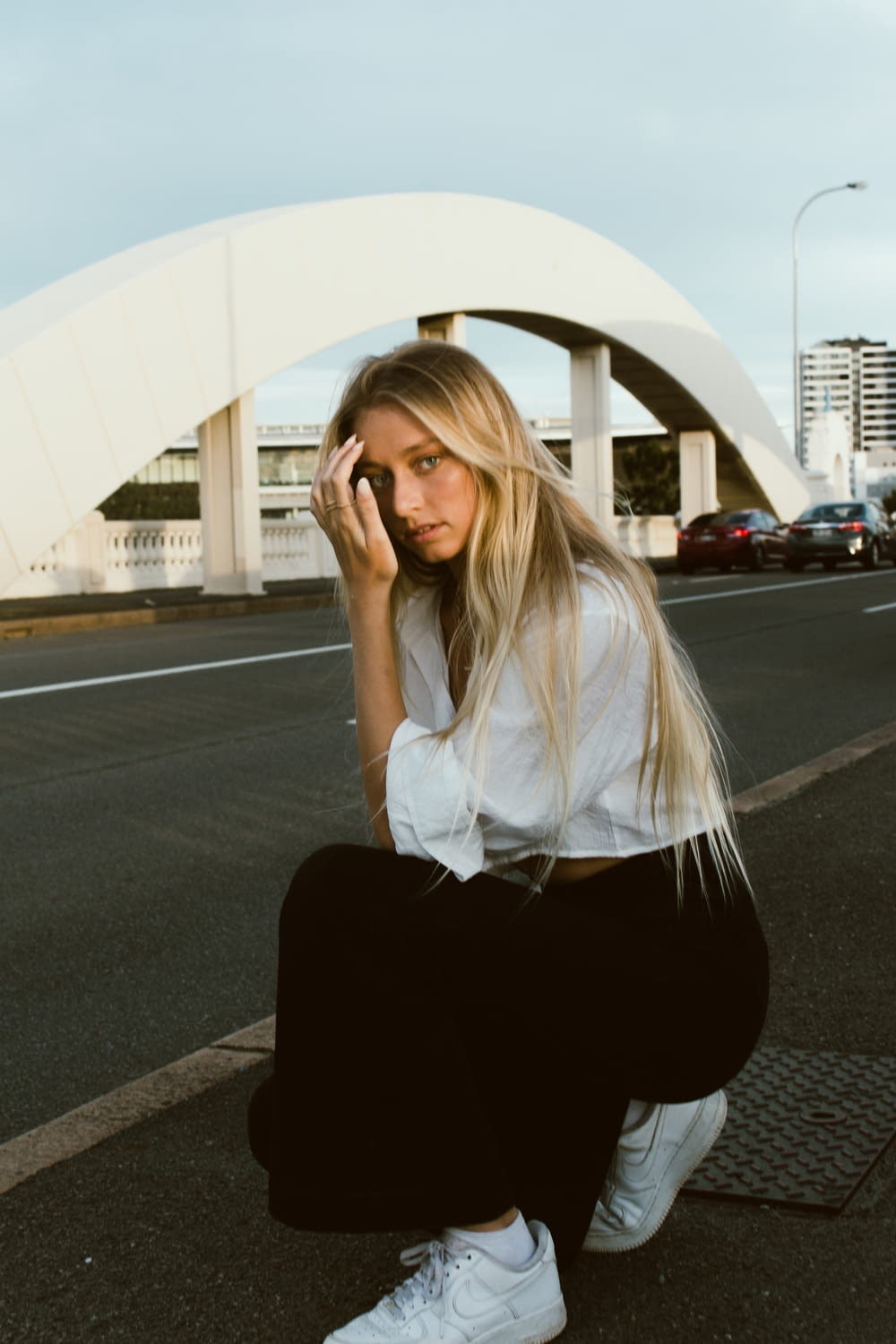 woman in white long sleeve shirt and black pants sitting on gray asphalt road during daytime