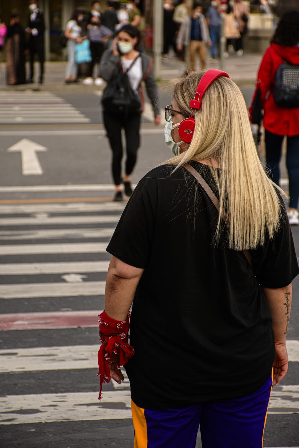 woman in black t-shirt and red boots walking on pedestrian lane during daytime