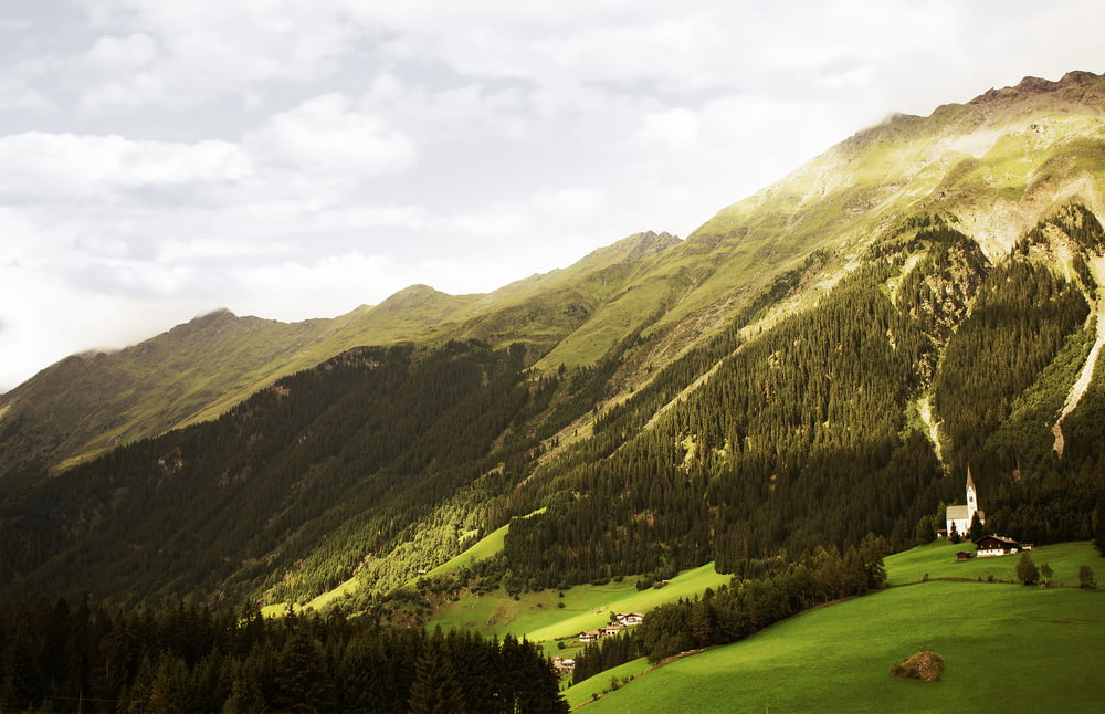 green mountains and trees under white cloudy sky during daytime