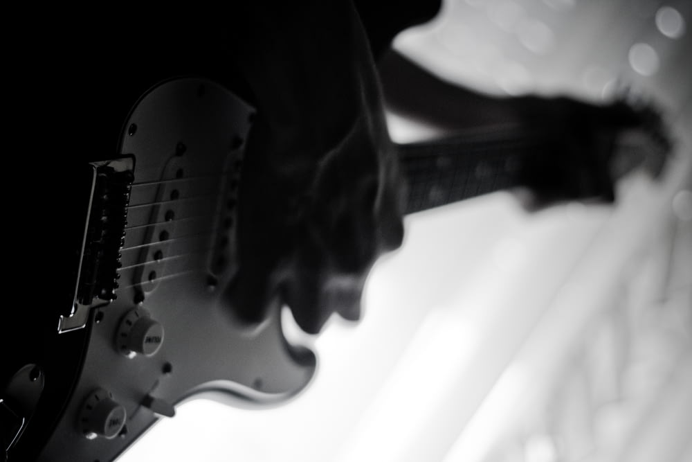 grayscale photo of person playing electric guitar