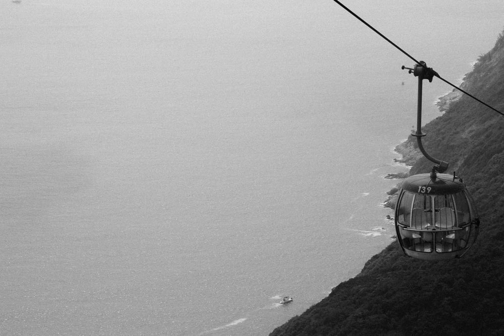 grayscale photography of cable car distance with sea
