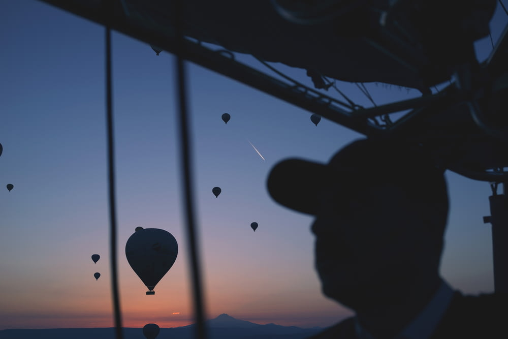 silhouette of person with hot air balloon in the air